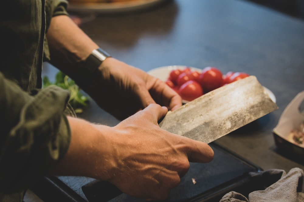 person holding a brown wooden chopping board with red round fruits