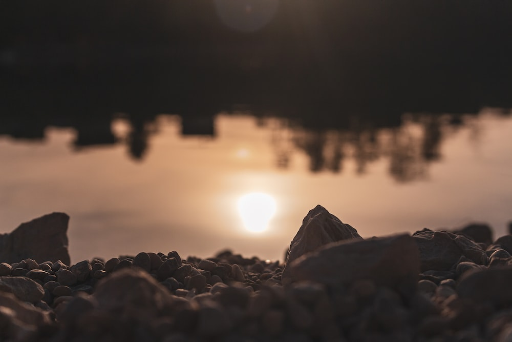 silhouette of rocks near body of water during sunset