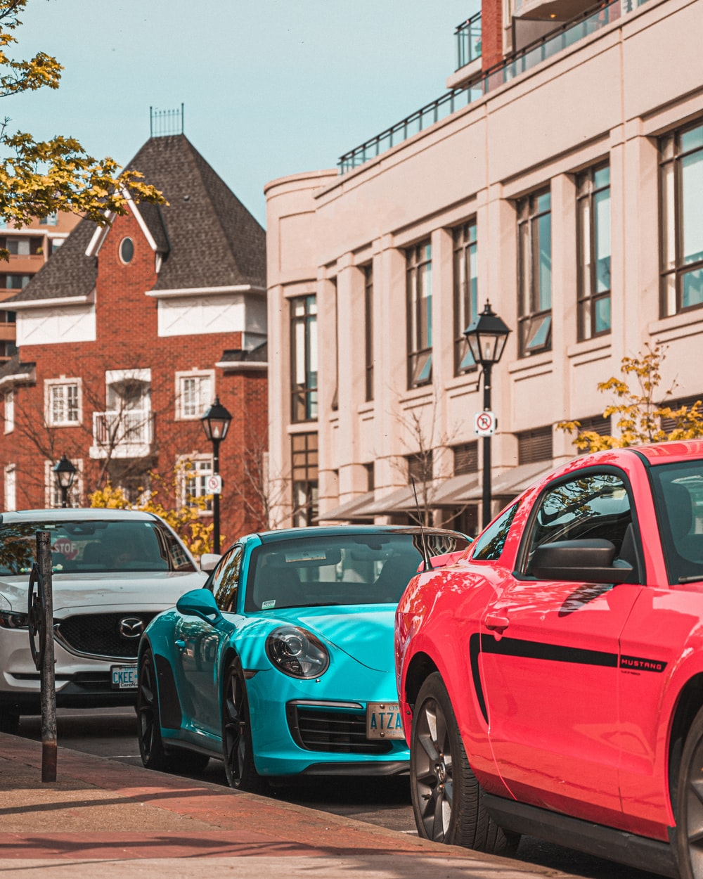 red and blue cars parked on sidewalk during daytime