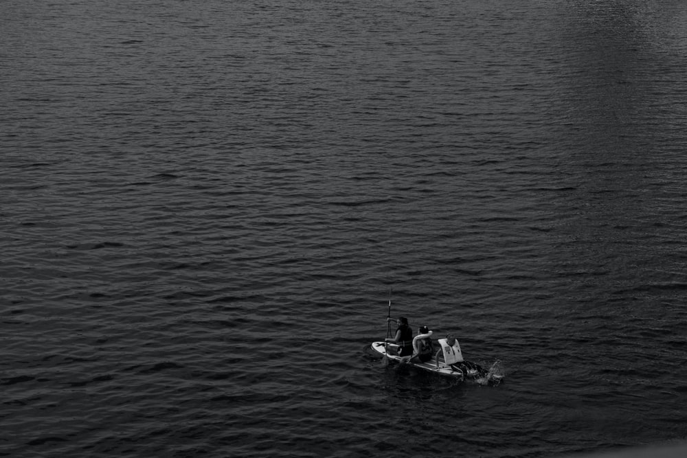 grayscale photo of man riding on boat on water