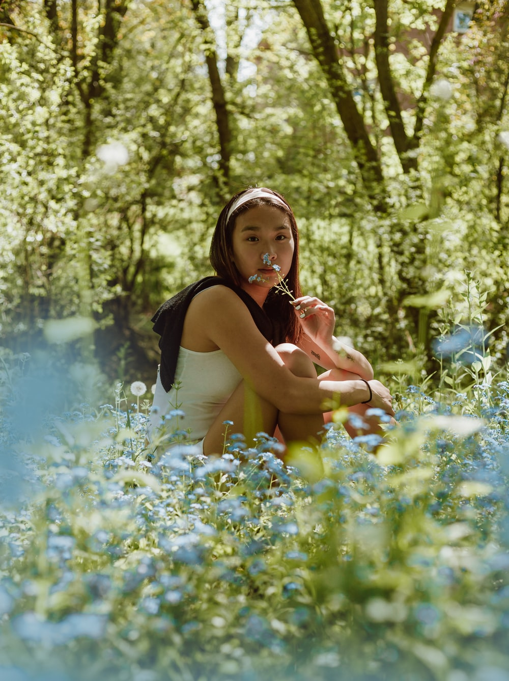 woman in black tank top sitting on blue flower field during daytime
