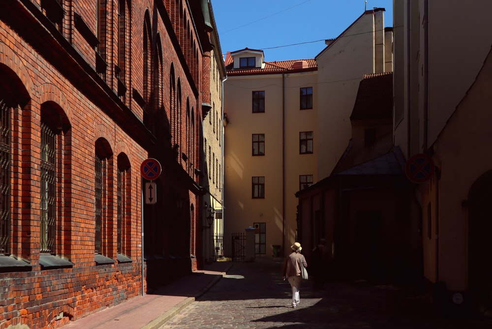 person in white coat walking on street during daytime
