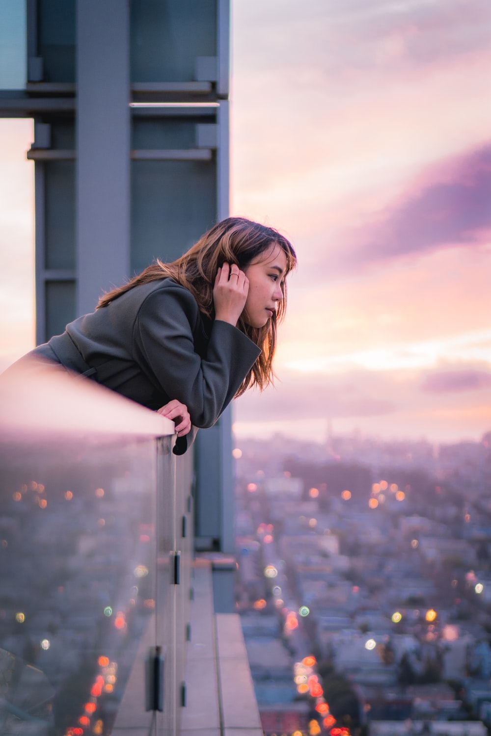 woman in black jacket standing on building during daytime