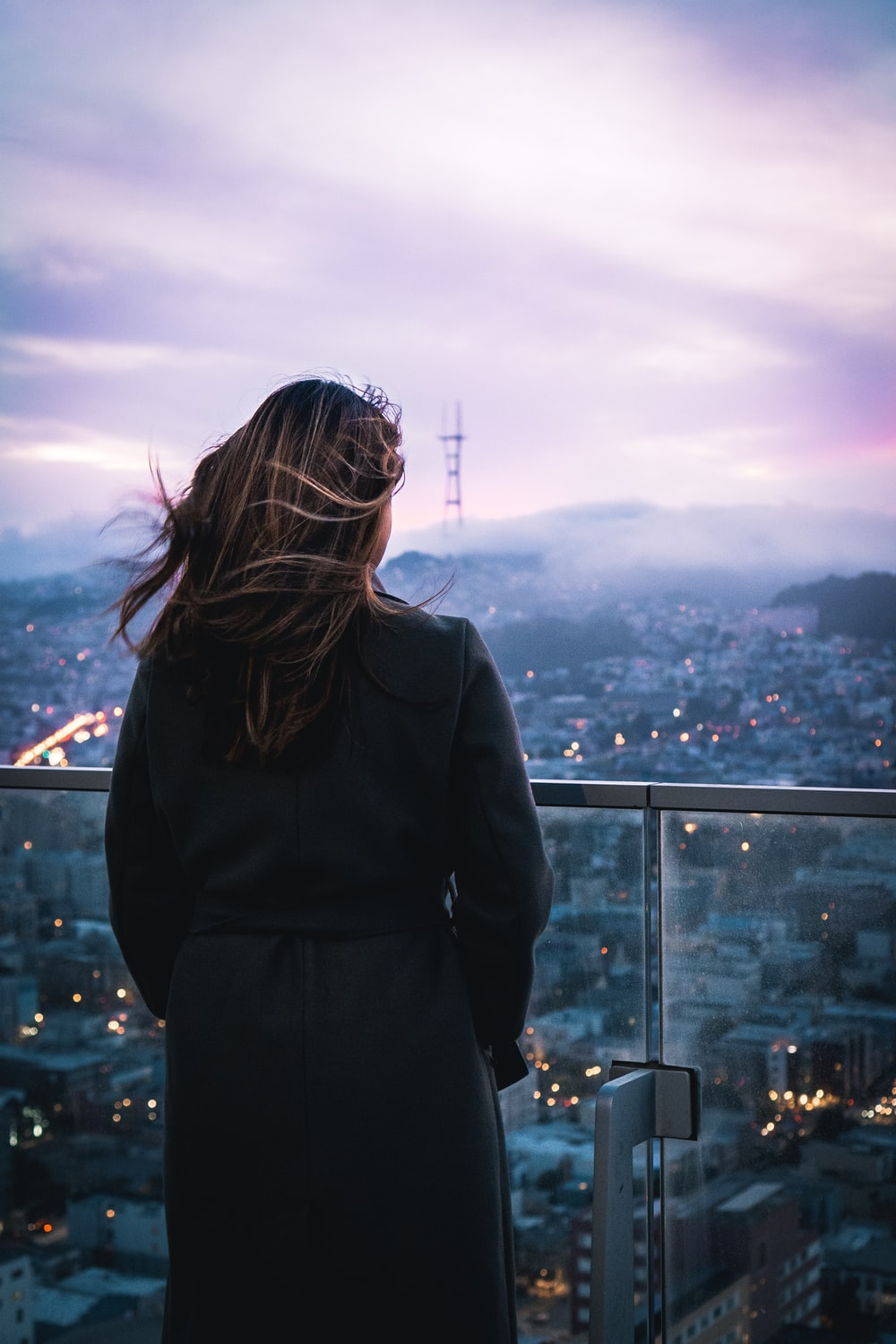 woman in black coat standing on top of building looking at the city during daytime