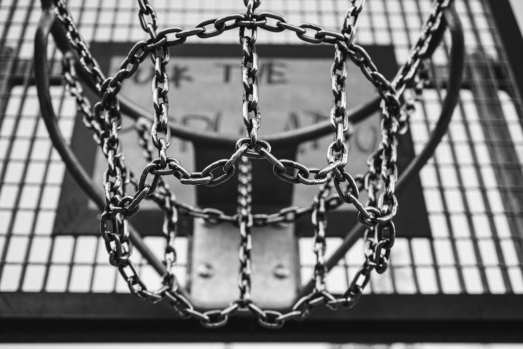A basketball hoop with its backboard on a streetcourt.