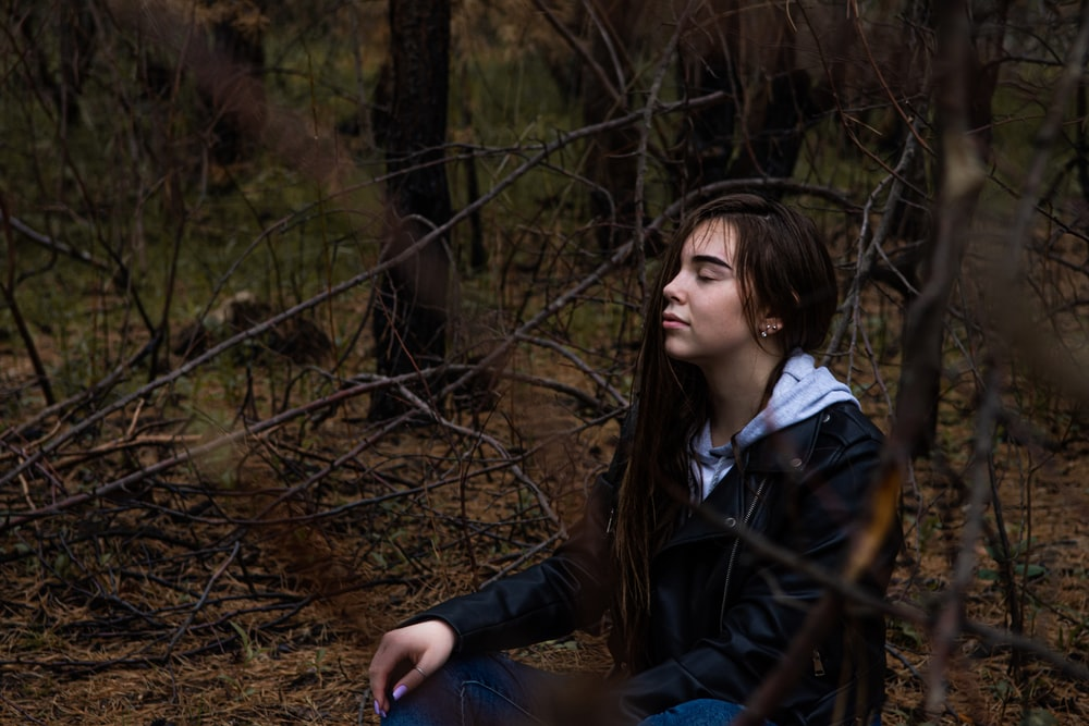 woman in black jacket sitting on brown grass during daytime