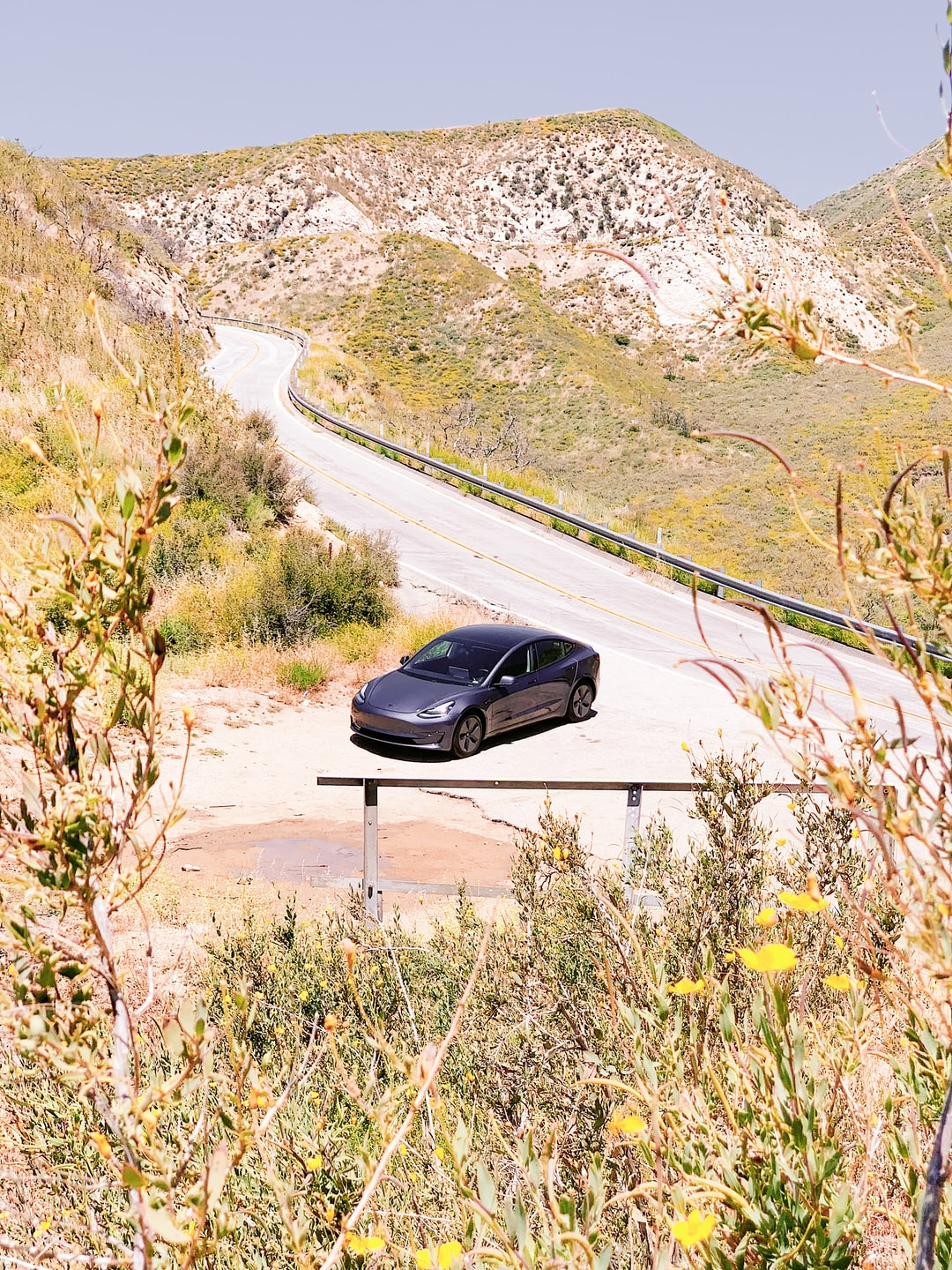 Tesla Model 3 Gray in Desert by Road looked at from a hill with mountains in background