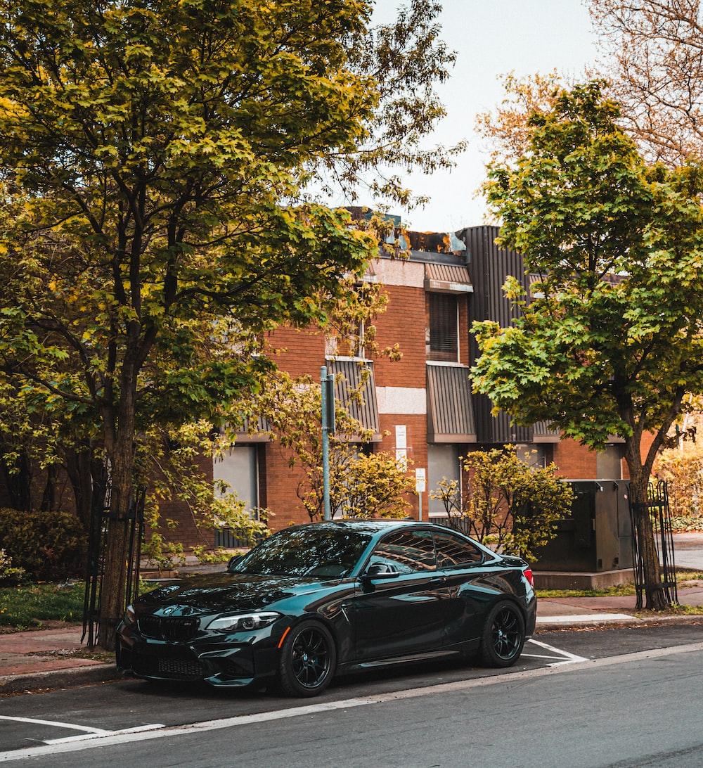 black sedan parked near brown concrete building during daytime