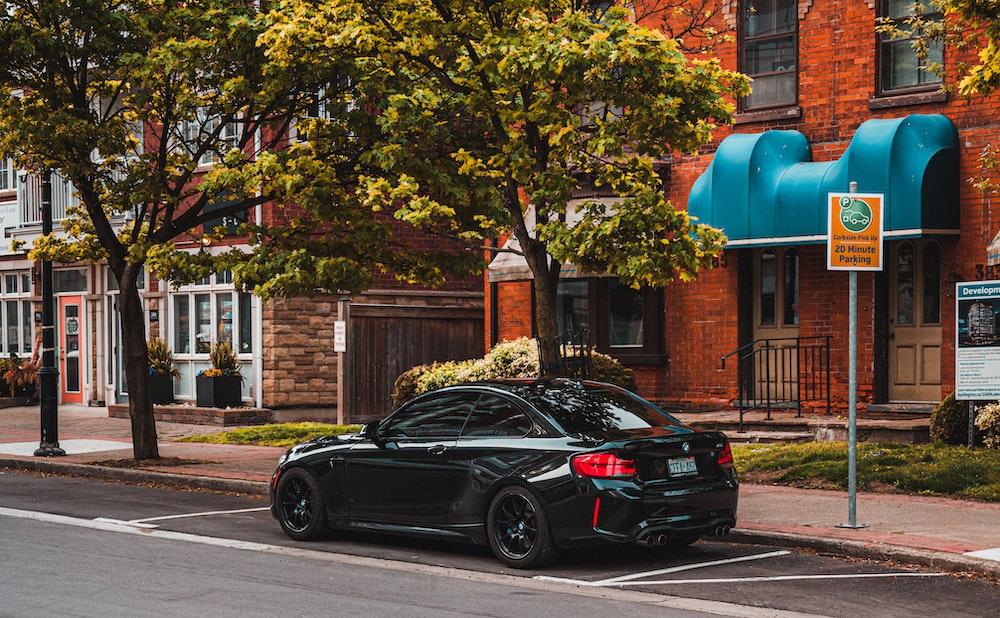 black sedan parked beside green tree during daytime