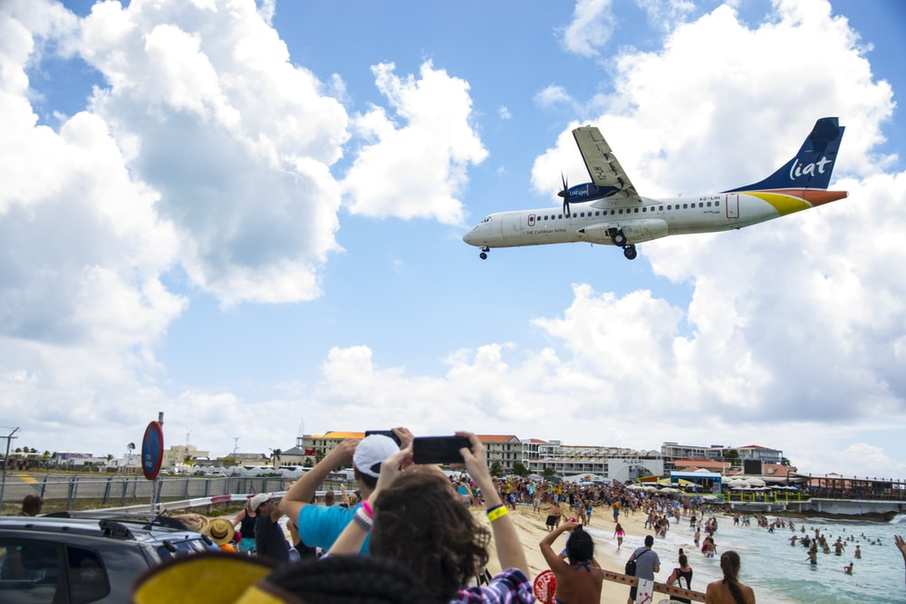 people gathering near airplane under blue sky during daytime