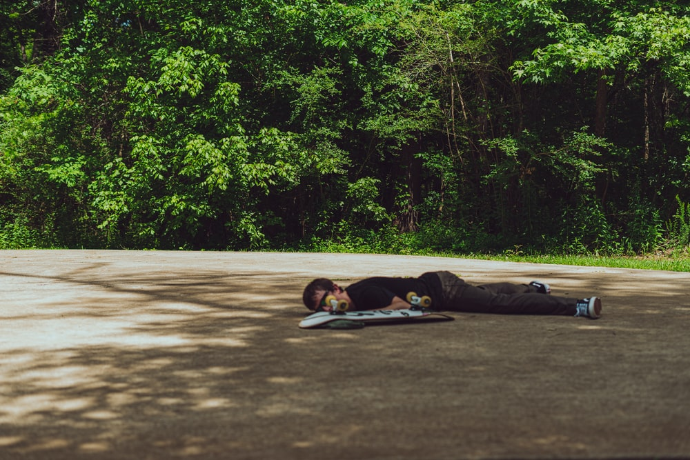 man lying on gray concrete road during daytime