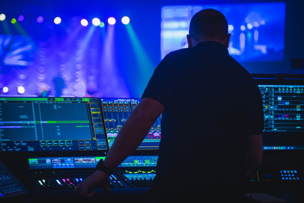 man in black t-shirt playing audio mixer