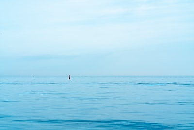 person in red shirt standing on blue sea during daytime