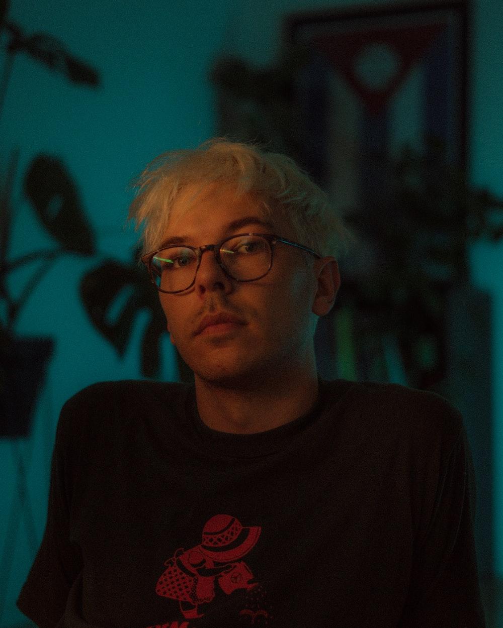 man in black crew neck shirt wearing black framed eyeglasses