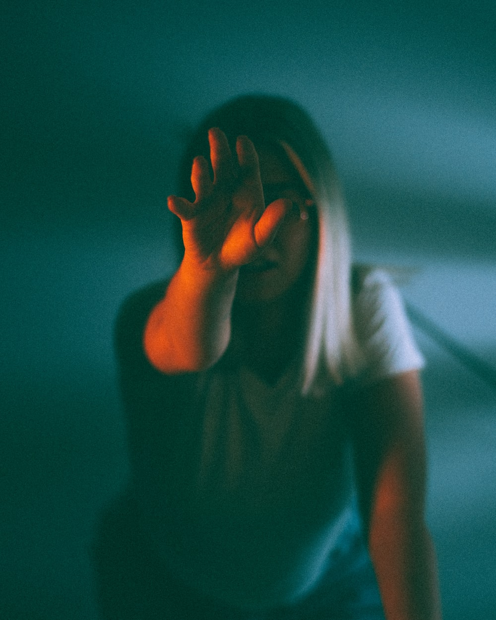 woman in white t-shirt covering her face