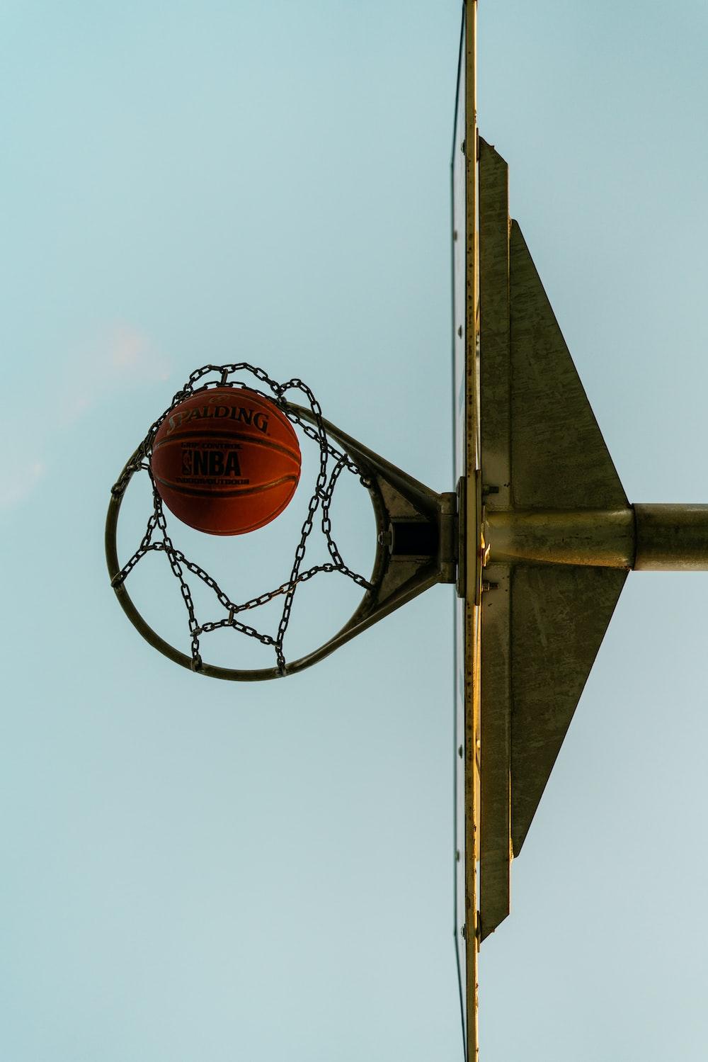 basketball on basketball hoop under blue sky during daytime