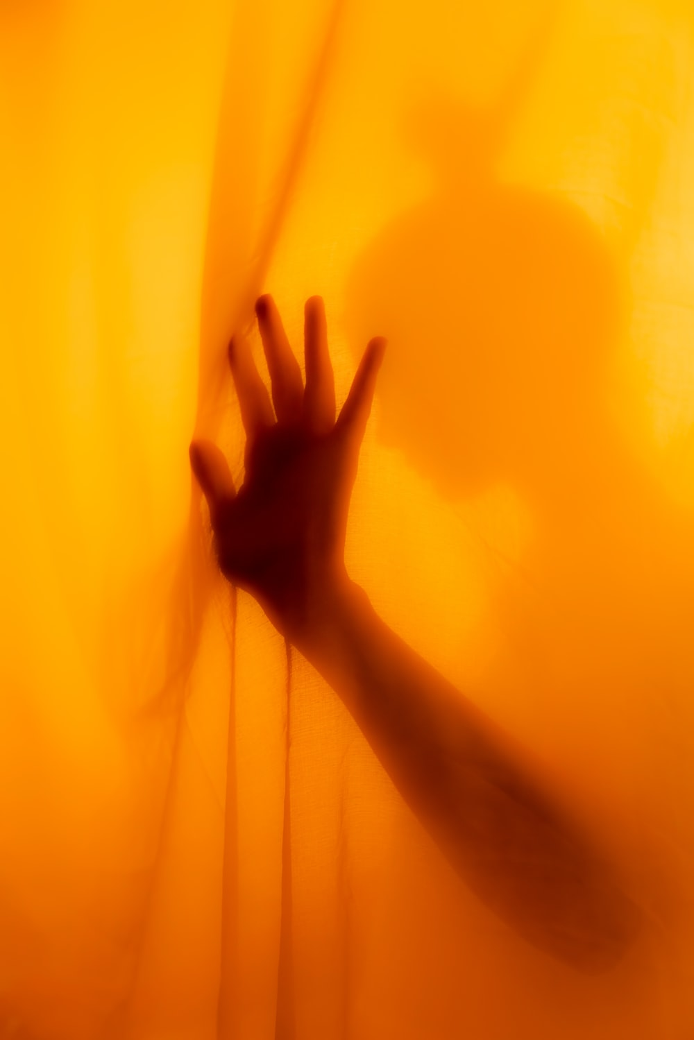 persons hand on yellow textile