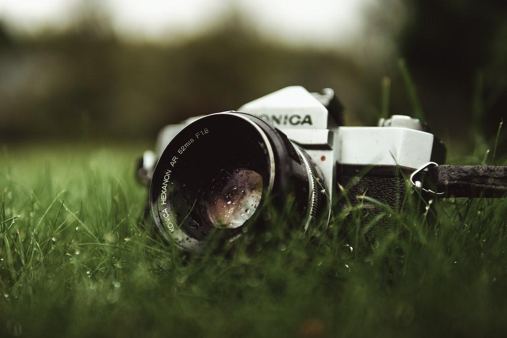 black and silver nikon dslr camera on green grass