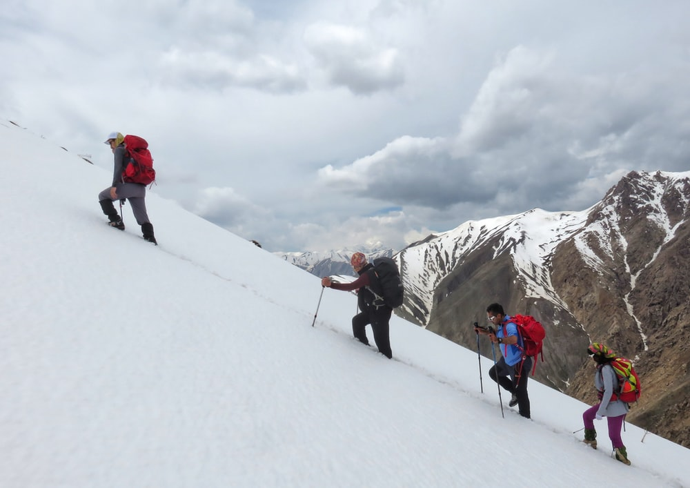 people hiking on snow covered mountain during daytime