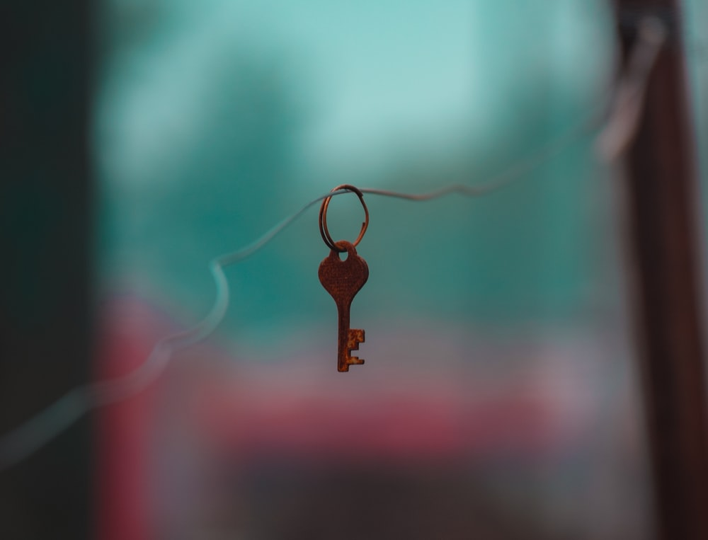 brown key chain with black and red background