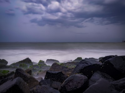 Puducherry rocky shore under cloudy sky during daytime