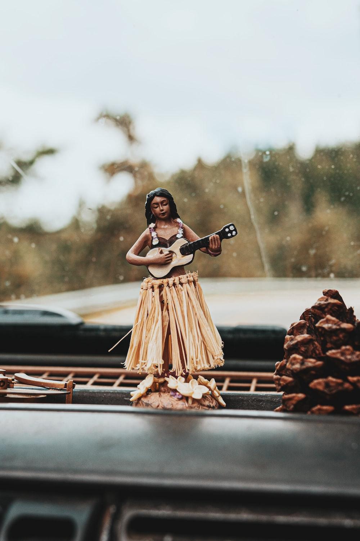 woman in brown dress sitting on black car hood during daytime