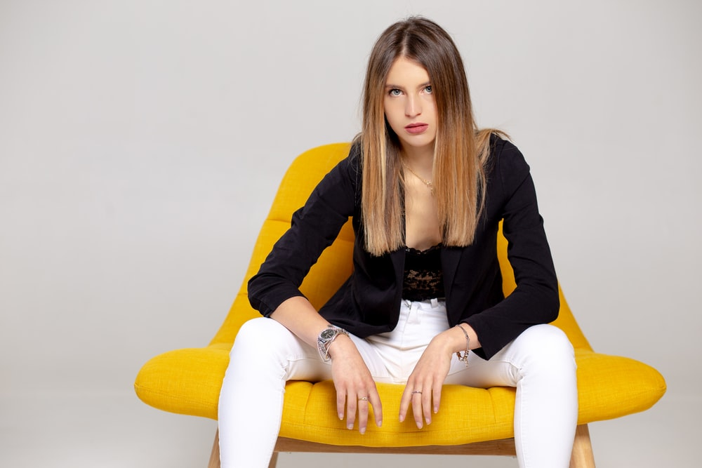 woman in black long sleeve shirt and white pants sitting on yellow couch