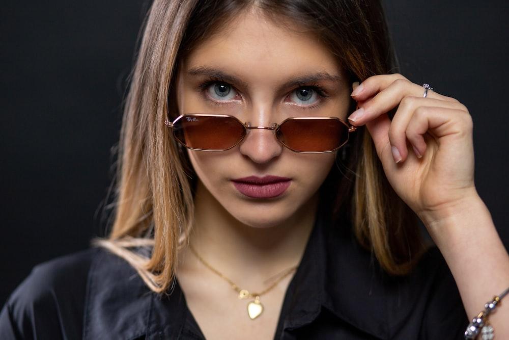 woman in black blazer wearing brown sunglasses