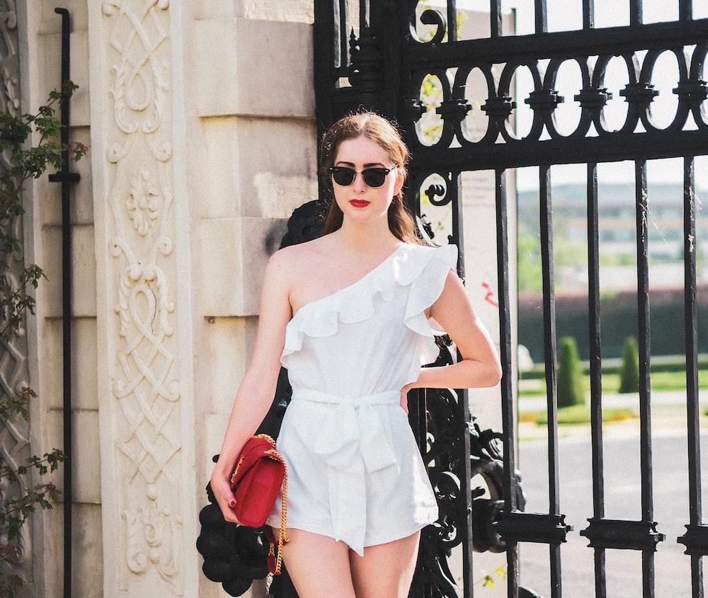 woman in white tank top and black denim shorts wearing sunglasses standing beside black metal gate