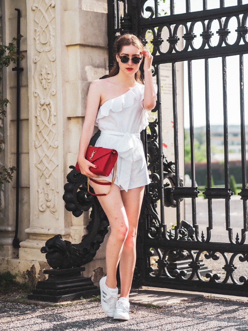 woman in white sleeveless dress wearing sunglasses standing near black metal gate during daytime