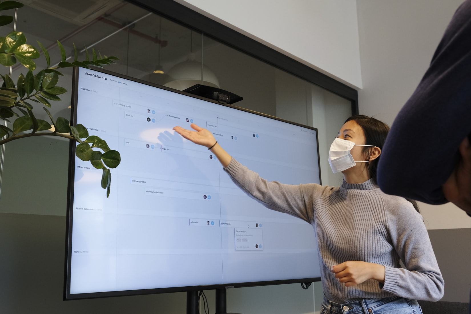 A woman pointing towards TV - virtual games to play with coworkers