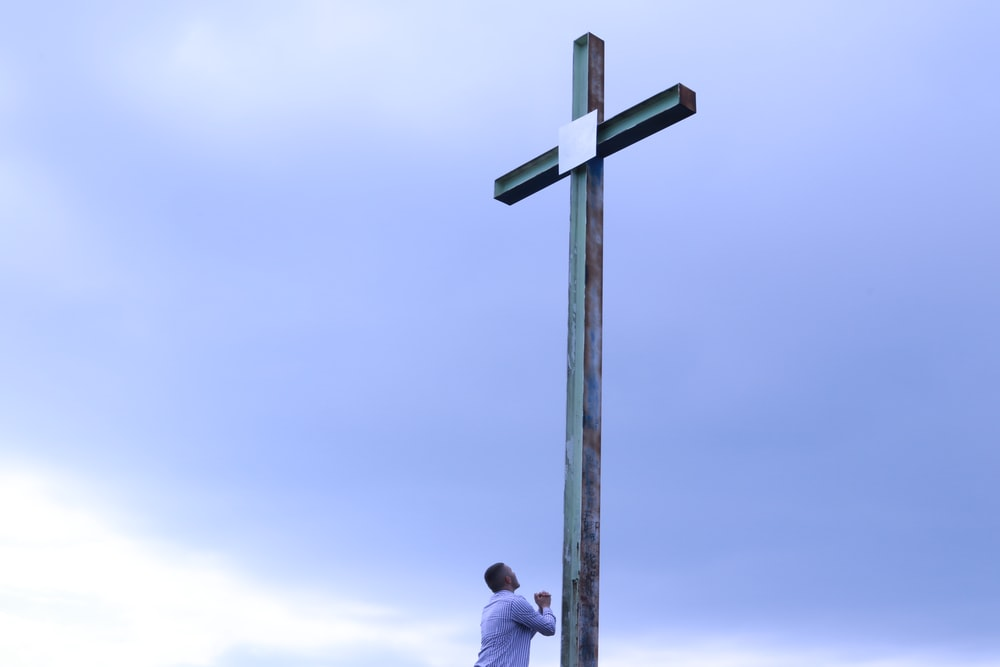 man in white shirt standing beside brown wooden cross under white clouds during daytime