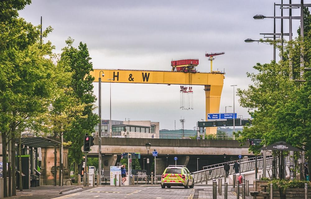 yellow and white crane near white and yellow bus during daytime