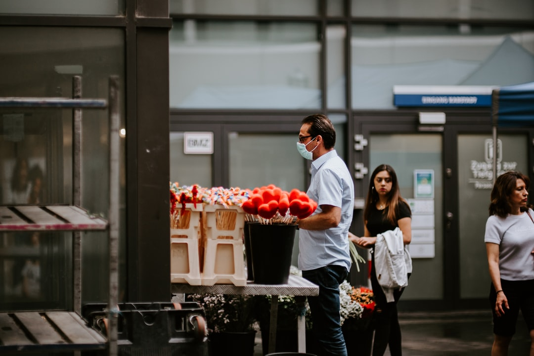 A man with face mask buying flowers.