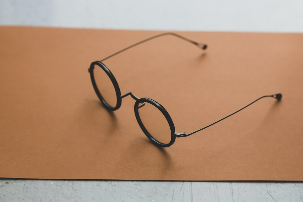 black framed eyeglasses on orange surface