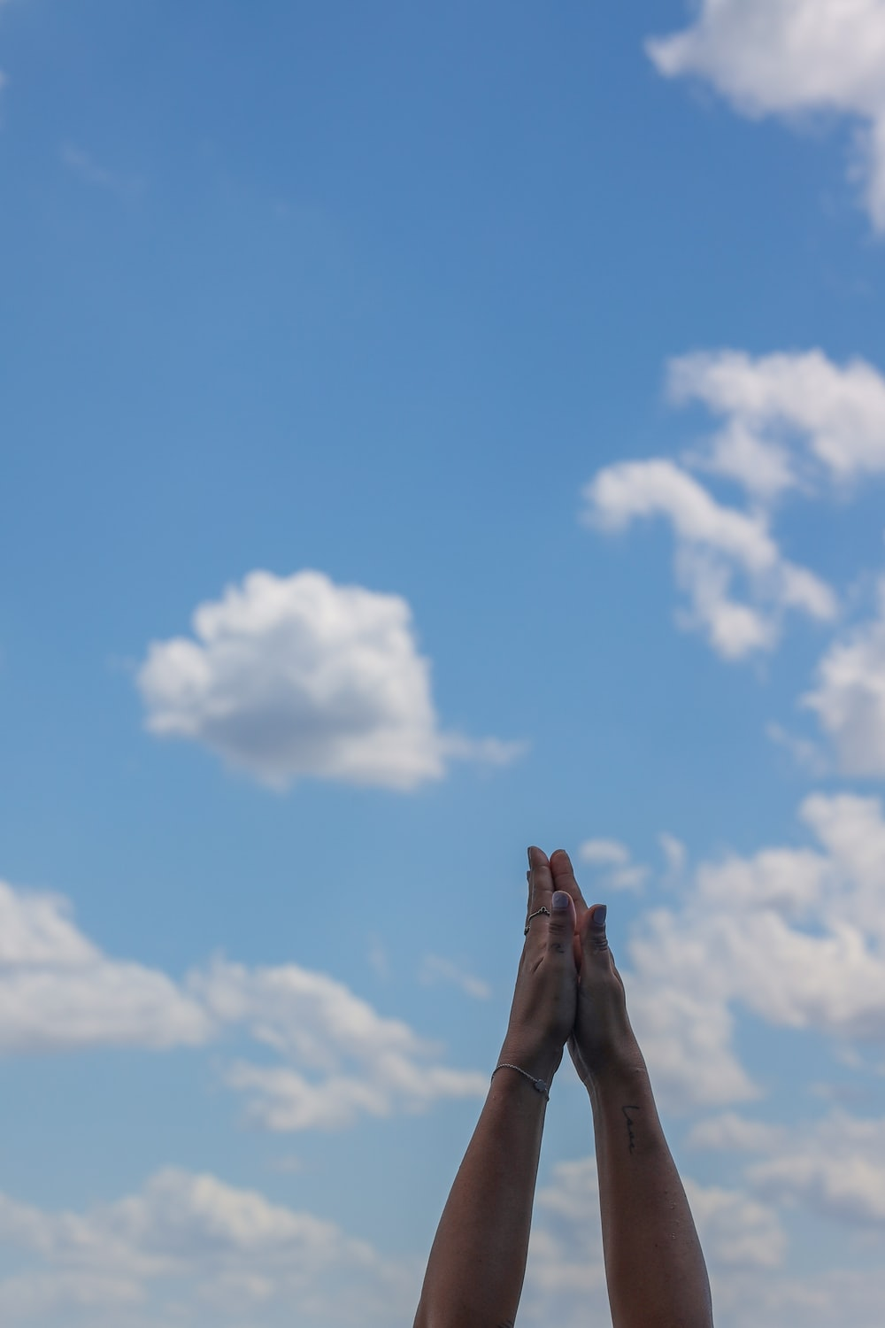 person raising his right hand under blue sky and white clouds during daytime