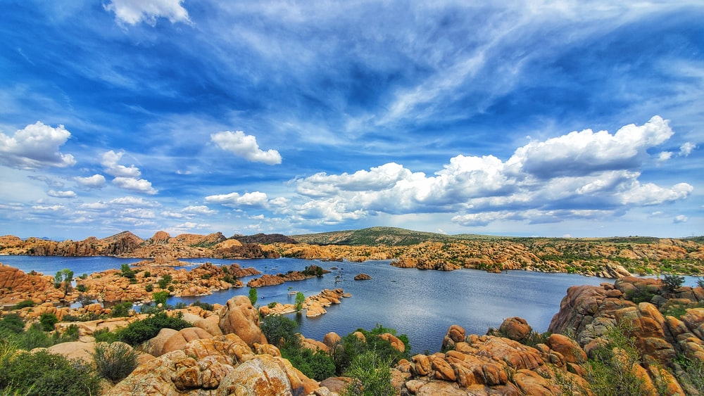 brown rocks on body of water under blue sky and white clouds during daytime