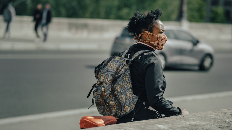 A photo of a woman out on the street with a patterned fabric mask on to protect from COVID. She is standing with her bike.