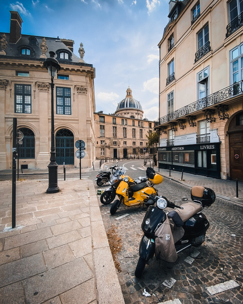 yellow and black sports bike parked beside black and yellow motorcycle near brown concrete building during