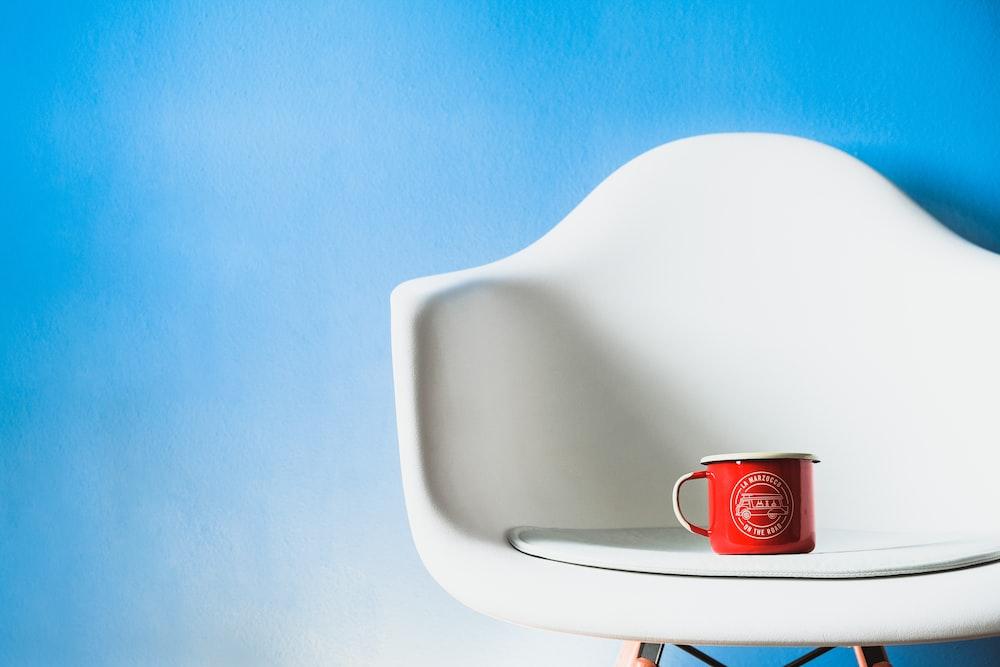 red ceramic mug on white ceramic sink