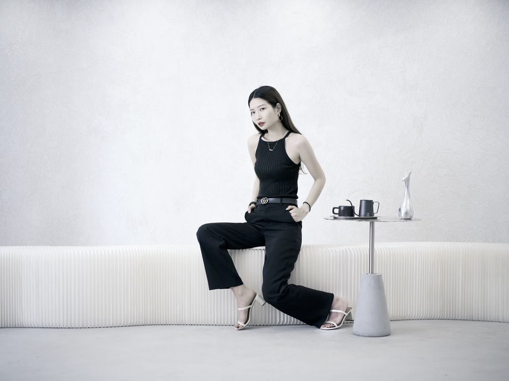 woman in black tank top and black pants sitting on white couch