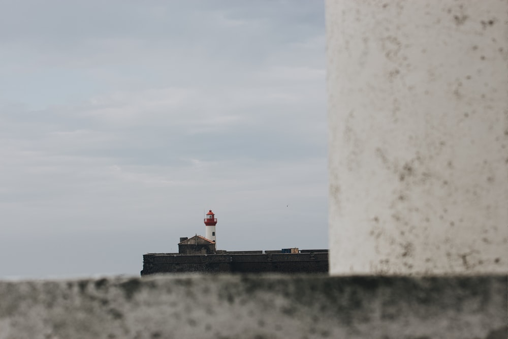 white and red lighthouse near body of water during daytime