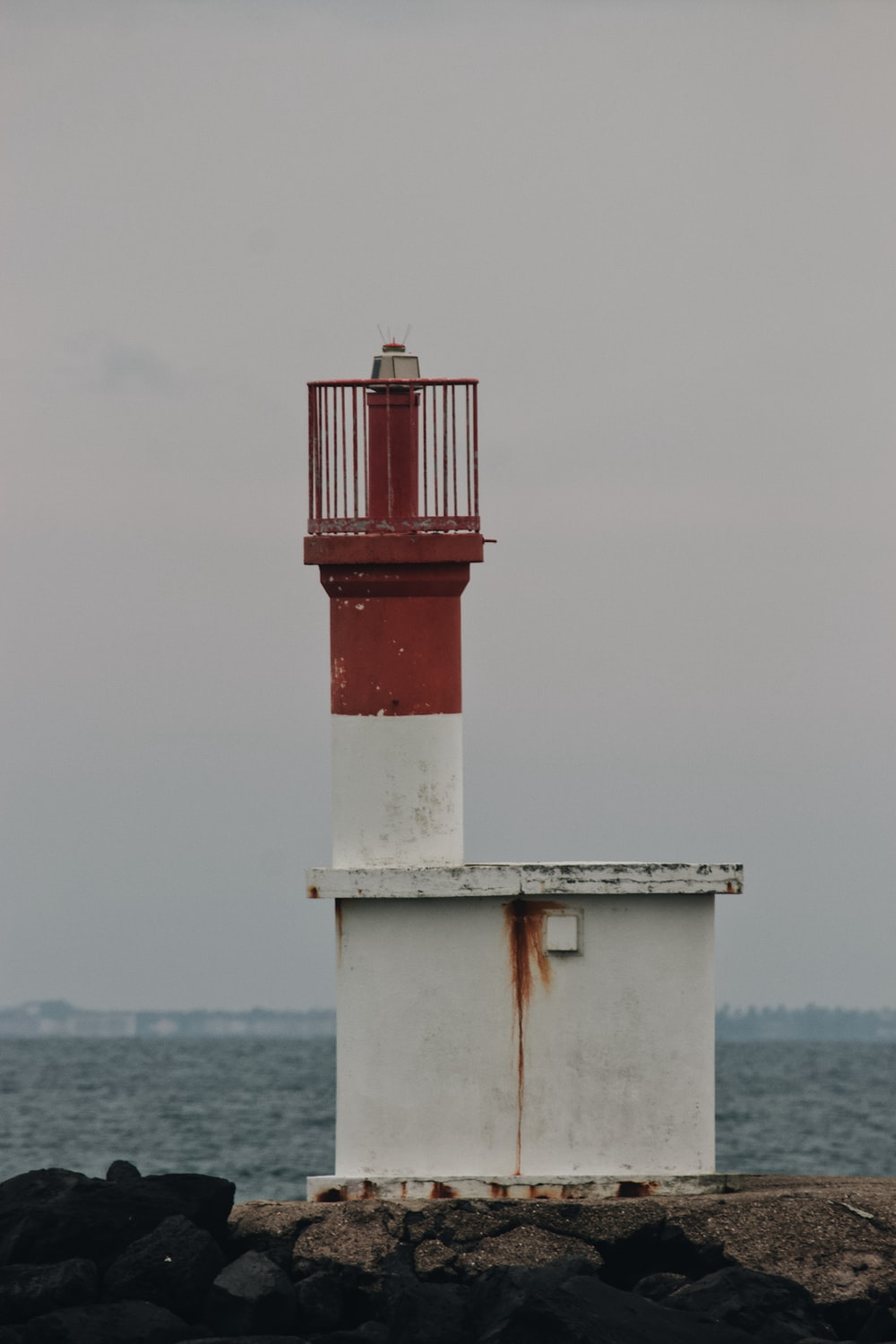 white and red lighthouse on the sea