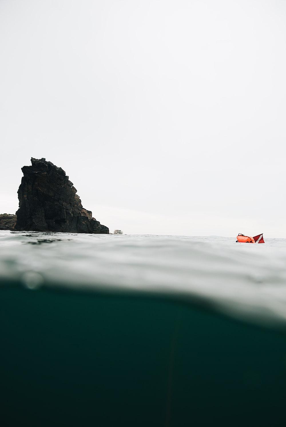 orange and white flag on black rock formation