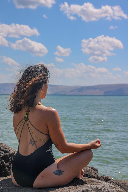 woman in black bikini sitting on rock near sea during daytime