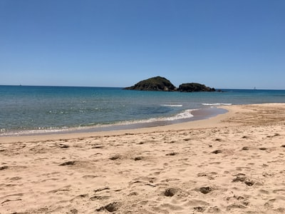 brown sand beach with blue ocean water under blue sky during daytime