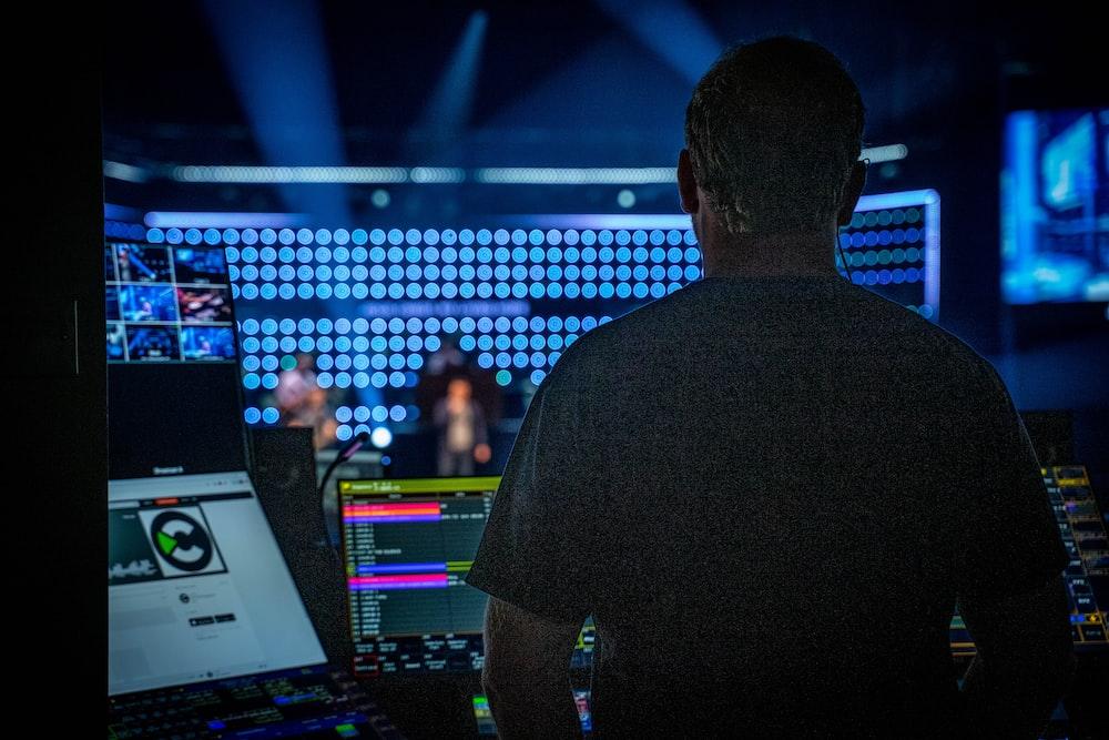 man in black shirt standing in front of audio mixer