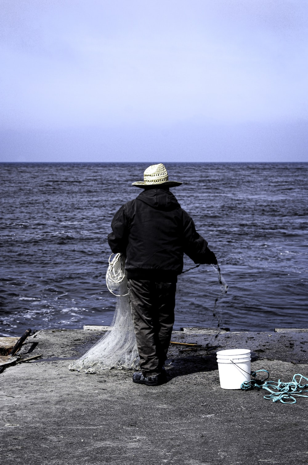 man in black jacket and brown hat holding stick near body of water during daytime
