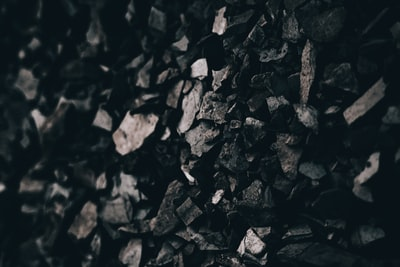 grayscale photo of pile of rocks coal teams background