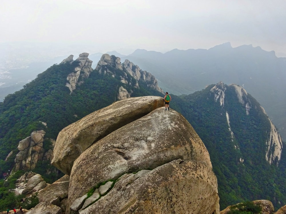 person in black jacket standing on gray rock mountain during daytime